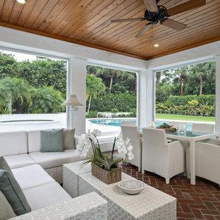 マイアミのトランジショナルスタイルのおしゃれなサンルーム (レンガの床、標準型天井、茶色い床) の写真