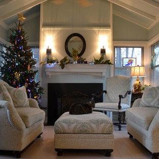 Cette photo montre une véranda chic de taille moyenne avec un sol en bois clair, une cheminée standard, un manteau de cheminée en bois et un plafond standard.