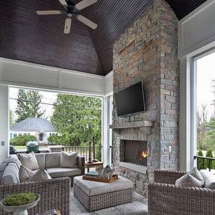 Idee per una grande veranda classica con camino classico, cornice del camino in pietra, soffitto classico e pavimento grigio
