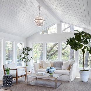 Cette photo montre une grand véranda chic avec un sol en bois clair, un plafond standard, un sol beige et aucune cheminée.
