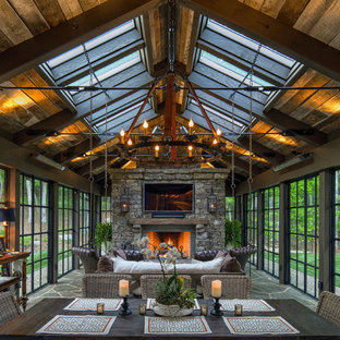 Inspiration for a large rustic green floor sunroom remodel in Charlotte with a stone fireplace and a skylight