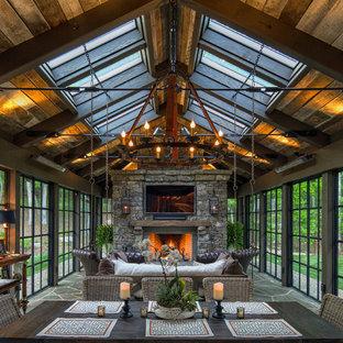 Ispirazione per una grande veranda rustica con cornice del camino in pietra, lucernario e pavimento verde