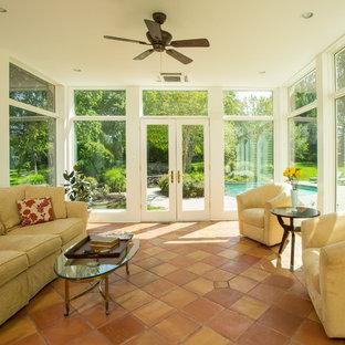 Idée de décoration pour une véranda tradition avec un sol en carreau de terre cuite, un plafond standard et un sol orange.