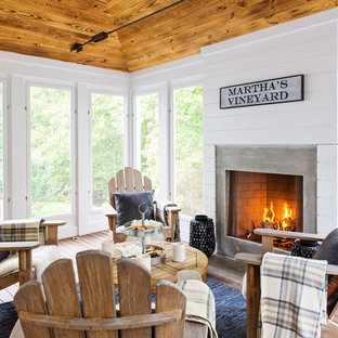 Coastal dark wood floor sunroom photo in Boston with a standard fireplace, a concrete fireplace and a standard ceiling