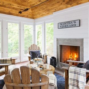 Idée de décoration pour une véranda marine avec un sol en bois foncé, une cheminée standard, un manteau de cheminée en béton et un plafond standard.