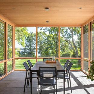 Réalisation d'une véranda tradition avec béton au sol, aucune cheminée, un plafond standard et un sol gris.