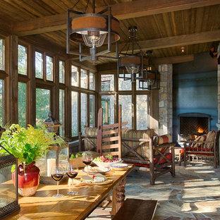 Idées déco pour une grand véranda montagne avec un sol en ardoise, une cheminée d'angle, un manteau de cheminée en métal et un plafond standard.