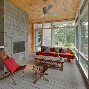 Ispirazione per una veranda minimalista di medie dimensioni con parquet chiaro, camino classico, soffitto classico, cornice del camino in cemento e pavimento grigio