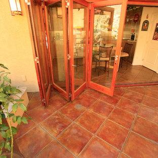 Aménagement d'une grand véranda campagne avec aucune cheminée, un plafond standard et un sol marron.