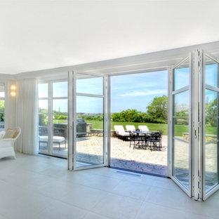 Réalisation d'une très grand véranda design avec un sol en carrelage de porcelaine et un plafond standard.