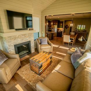 Réalisation d'une véranda avec un sol en bois brun, une cheminée standard, un manteau de cheminée en pierre de parement, un sol marron et un plafond standard.