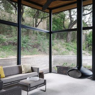 Idée de décoration pour une grand véranda minimaliste avec béton au sol, cheminée suspendue, un manteau de cheminée en métal, un plafond standard et un sol gris.