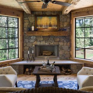 Cette image montre une véranda chalet avec une cheminée d'angle, un manteau de cheminée en pierre, un plafond standard, un sol beige et un sol en bois clair.