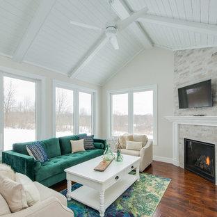 グランドラピッズの中くらいのトランジショナルスタイルのおしゃれなサンルーム (無垢フローリング、コーナー設置型暖炉、タイルの暖炉まわり、茶色い床) の写真