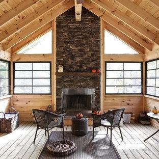 Esempio di una veranda rustica con pavimento in legno massello medio, soffitto classico, cornice del camino in metallo e pavimento marrone