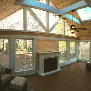Idée de décoration pour une véranda craftsman de taille moyenne avec un sol en bois brun, une cheminée standard, un manteau de cheminée en bois, un puits de lumière et un sol marron.