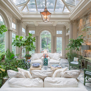 Cette photo montre une très grand véranda chic avec aucune cheminée, un plafond en verre et un sol multicolore.