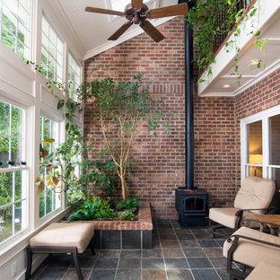 Klassisk inredning av ett mellanstort uterum, med klinkergolv i keramik, en öppen vedspis, takfönster och flerfärgat golv