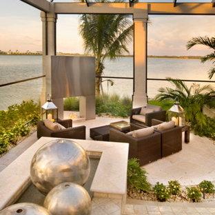 マイアミの中くらいのビーチスタイルのおしゃれなサンルーム (コンクリートの床、コンクリートの暖炉まわり、ベージュの床) の写真