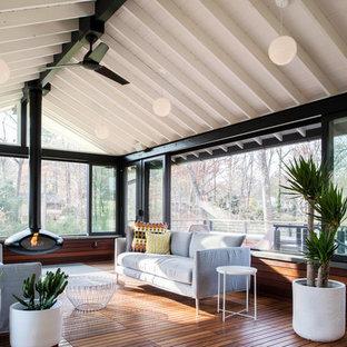 50 tals inredning av ett uterum, med en hängande öppen spis, tak och mellanmörkt trägolv