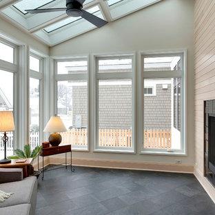 Bild på ett mellanstort vintage uterum, med en dubbelsidig öppen spis, en spiselkrans i trä, takfönster, klinkergolv i keramik och grått golv