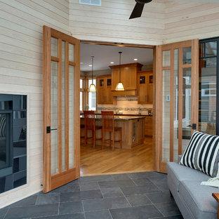 ミネアポリスの中くらいのトランジショナルスタイルのおしゃれなサンルーム (両方向型暖炉、タイルの暖炉まわり、天窓あり、セラミックタイルの床) の写真