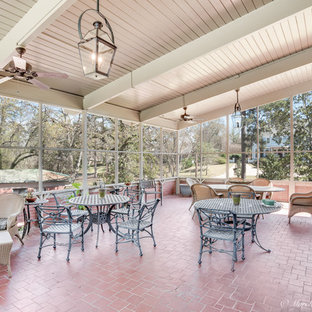 Huge elegant brick floor sunroom photo in New Orleans with no fireplace and a standard ceiling