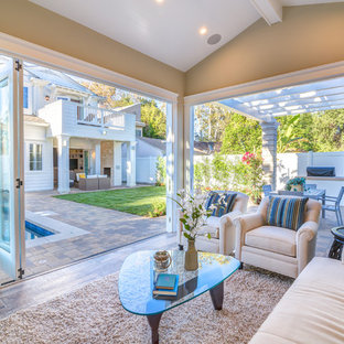 This is an example of a small classic conservatory in Los Angeles with laminate floors, a standard ceiling, brown floors, a standard fireplace and a brick fireplace surround.