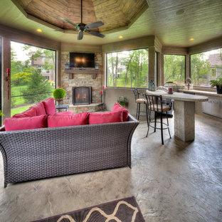 Idee per una veranda mediterranea con cornice del camino in pietra, soffitto classico, pavimento in cemento e pavimento grigio