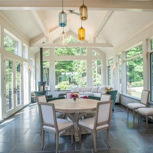 Ejemplo de galería de estilo de casa de campo, grande, con suelo de baldosas de porcelana, marco de chimenea de metal, techo estándar, suelo gris y estufa de leña