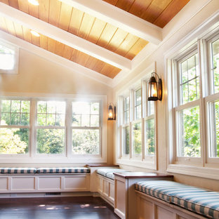 Cette photo montre une grand véranda chic avec un sol en bois foncé, une cheminée standard et un plafond standard.