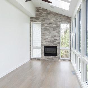 Foto på ett funkis uterum, med ljust trägolv, en bred öppen spis, en spiselkrans i trä, takfönster och grått golv