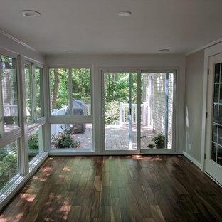 Inspiration pour une véranda traditionnelle de taille moyenne avec sol en stratifié, un plafond standard et un sol marron.