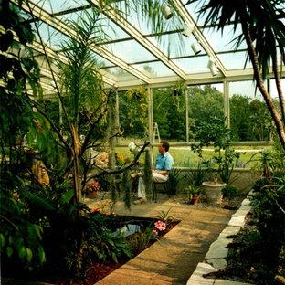 Exemple d'une véranda de taille moyenne avec un plafond en verre et un sol en carreau de terre cuite.