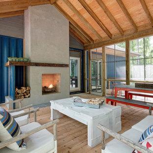 Réalisation d'une véranda chalet avec un sol en bois clair, une cheminée standard, un manteau de cheminée en béton et un plafond standard.