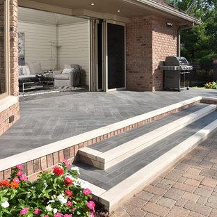 Ispirazione per una veranda con camino ad angolo, cornice del camino in legno, soffitto classico e pavimento grigio