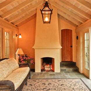Exemple d'une véranda chic de taille moyenne avec un sol en ardoise, une cheminée standard, un manteau de cheminée en plâtre et un sol gris.