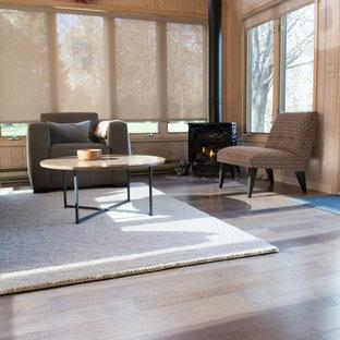 Ejemplo de galería rural, de tamaño medio, con suelo laminado, marco de chimenea de metal, techo estándar, suelo multicolor y estufa de leña