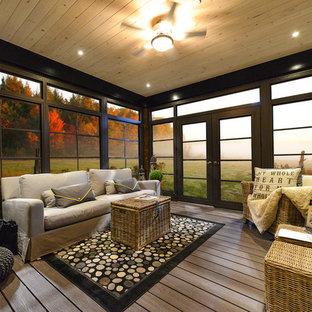 Foto di una veranda chic di medie dimensioni con pavimento in legno massello medio, stufa a legna, cornice del camino in metallo, soffitto classico e pavimento marrone