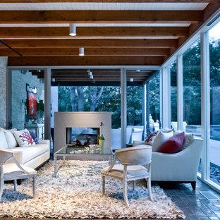 Aménagement d'une véranda rétro de taille moyenne avec une cheminée double-face et un plafond standard.