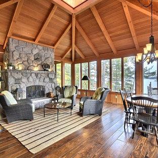 Inspiration pour une grand véranda chalet avec un sol en bois foncé, une cheminée double-face, un manteau de cheminée en pierre et un plafond standard.