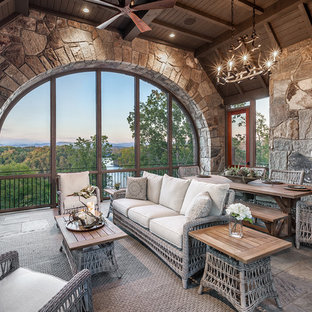 Foto på ett stort rustikt uterum, med kalkstensgolv, en standard öppen spis, en spiselkrans i sten, tak och grått golv