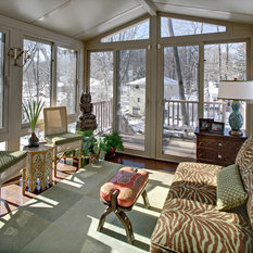 Eclectic Sunroom Cairns This tiny enclosed sun porch got a makeover: loveseat reupholstered in zebra, area rug, Moroccan camel saddle & side tables, wicker side chairs and custom ...