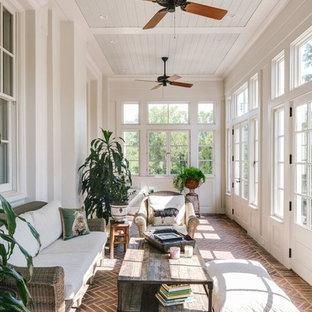 Immagine di una grande veranda classica con pavimento in mattoni, soffitto classico, nessun camino e pavimento rosso