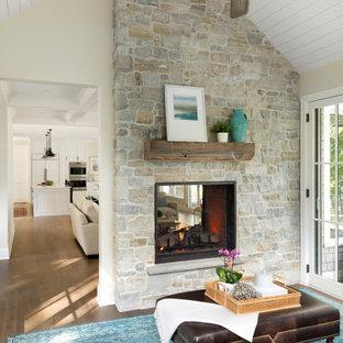 Exemple d'une grand véranda chic avec un sol en bois brun, une cheminée double-face, un manteau de cheminée en pierre, un plafond standard et un sol gris.
