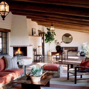 Idée de décoration pour une grand véranda sud-ouest américain avec un sol en carreau de terre cuite, une cheminée standard, un plafond standard et un manteau de cheminée en brique.