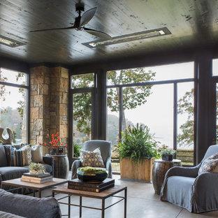 Idee per una grande veranda rustica con pavimento in cemento e pavimento grigio