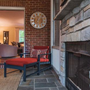 Idée de décoration pour une véranda tradition de taille moyenne avec un sol en ardoise, une cheminée standard, un manteau de cheminée en pierre de parement, un plafond standard et un sol gris.