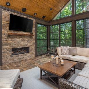 ローリーの大きいラスティックスタイルのおしゃれなサンルーム (横長型暖炉、石材の暖炉まわり、標準型天井、茶色い床) の写真