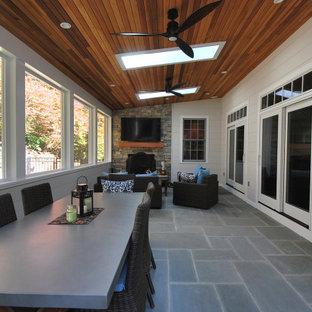 Aménagement d'une véranda contemporaine de taille moyenne avec un sol en ardoise, une cheminée standard, un manteau de cheminée en pierre, un puits de lumière et un sol bleu.